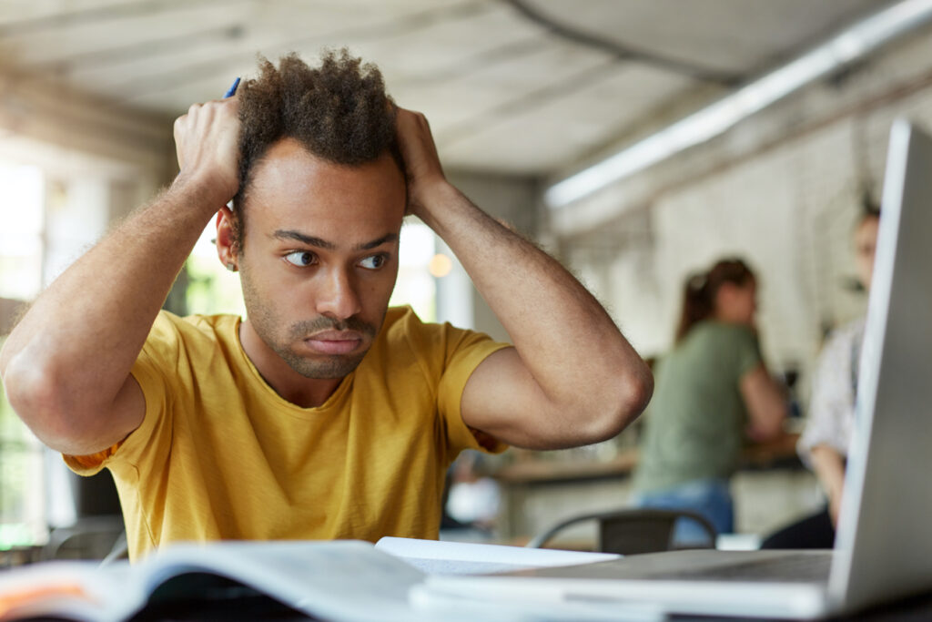 stressed young african american student feeling frustrated sitting coworking space front open laptop computer holding head with hands 1024x683 1